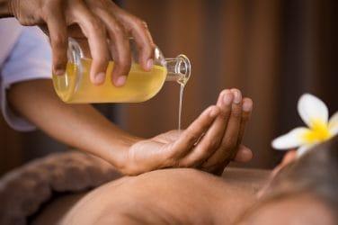 massageolie wordt in een hand geschonken boven een massageklant