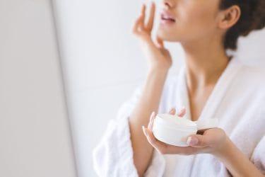 Vrouw smeert dagcrème op haar gelaat