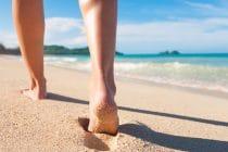 voeten van iemand die over het strand wandelt
