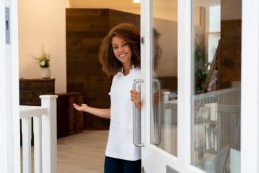 beauty professional doet vriendelijk de deur open voor een klant