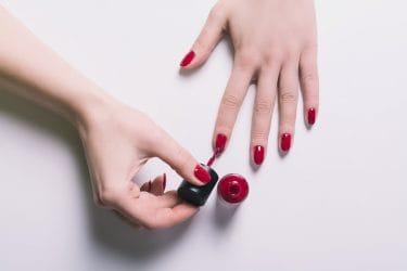 handen van een vrouw die rode nagellak aanbrengt