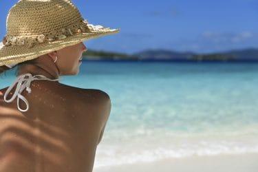 vrouw met hoed zit in de schaduw op een tropisch strand