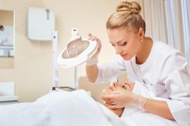 Schoonheidsspecialiste voert een huidanalyse uit in een beauty salon