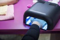 klant houdt nagels met gel in UV-lamp om de gel uit te harden.
