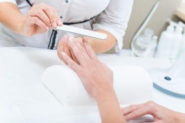 manicure bereidt handen van klant voor op dip powder nails behandeling