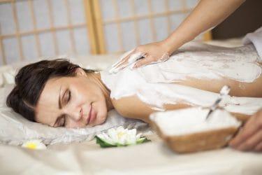 Vrouw krijgt lichaamspakking in beauty salon als nazomerse beauty behandeling