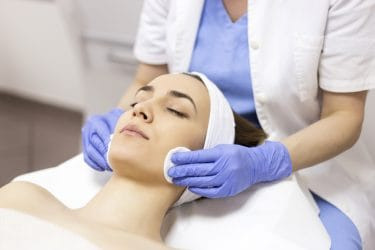 vrouw ontvangt een beauty behandeling voor het verminderen van acnelittekens.