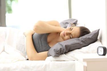 vrouw in bed met fibromyalgie klachten, pijn in nek