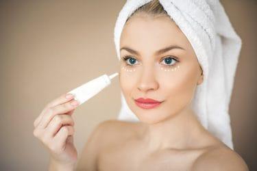 vrouw brengt een serum aan onder haar ogen