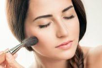 Jonge vrouw brengt make-up aan met kwast