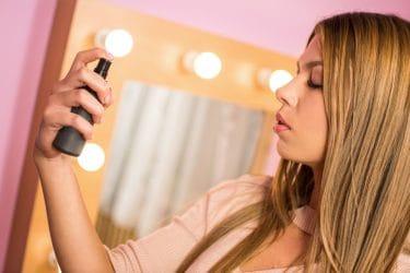 Vrouw fixeert haar make-up door setting spray over haar gelaat te sprayen