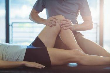 sportmasseur voert behandeling uit rond de knie om spierpijn te verminderen