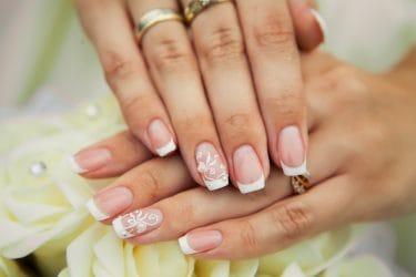 gelnagel van een bruidje op haar trouwdag. Het gaat om een French manicure met een patroontje en steentje.