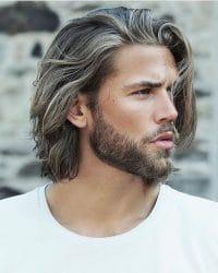 man met half lange haren, als een van de hippe mannenkapsels in 2020.