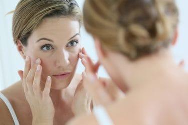 Vrouw van middelbare leeftijd brengt anti-rimpelcrème aan