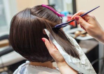 Vrouw met bobkapsel ondergaat een hair colouring behandeling in een kapsalon.