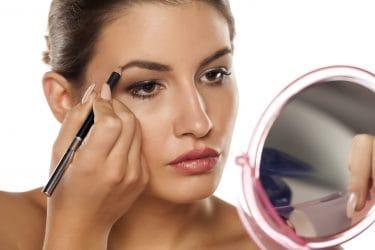 Jonge vrouw voor de spiegel die bezig is met haar wenkbrauwen bijwerken met een wenkbrauwpotlood.