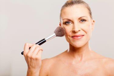 Vrouw brengt make-up aan om rimpels te camoufleren.