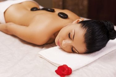 Jonge vrouw ondergaat veilig een hot stone massage zonder contra-indicaties