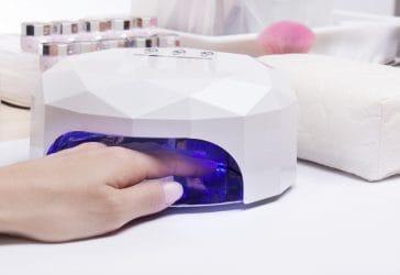 Klant houdt nagels onder een UV-lamp in een nagelstudio